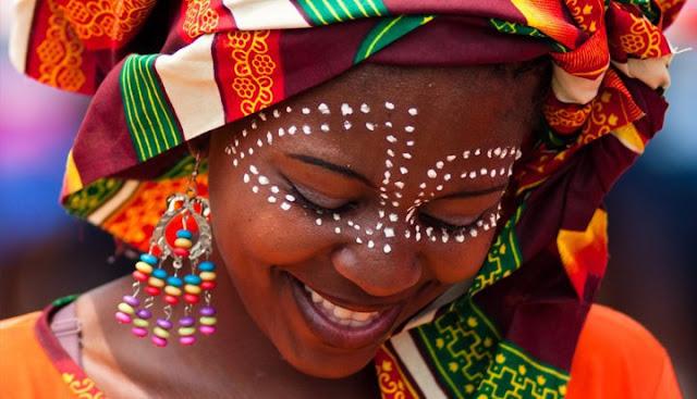moça negra com turbante sorrindo