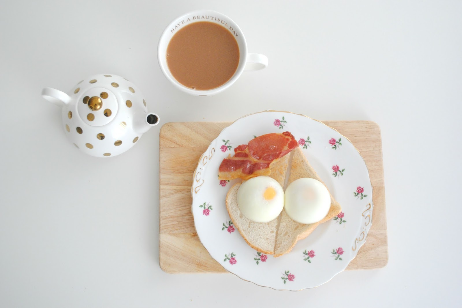 gold polka dot teapot and tea cup wooden board poached egg breakfast bacon rasher rose plate homeware