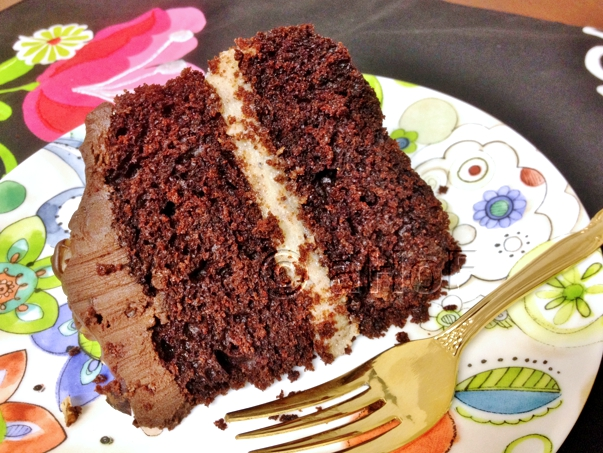 A slice of Chocolate Beet Cake, revised, with Hazelnut Creme Filling and Sour Cream Chocolate Ganache