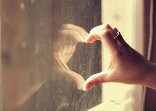 Mulher formando um coração com o reflexo do espelho