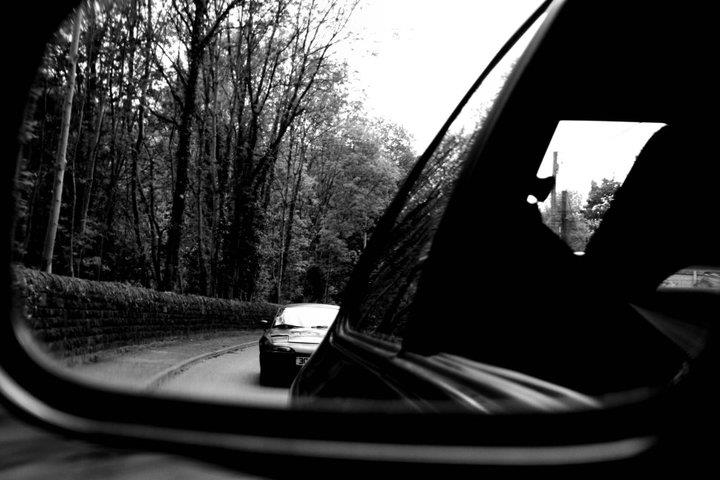 black and white photo of a sports car in the wing mirror of another car