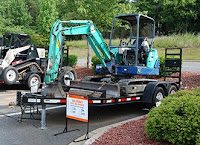 """Excavator on a trailer with """"for sale"""" sign"""