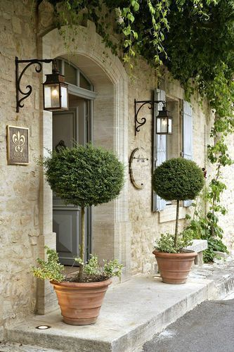Curb appeal alert! Topiaries in pots at arched entrance of #Frenchfarmhouse with blue shutters on Hello Lovely Studio