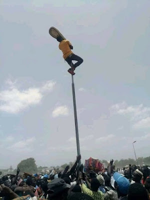 Drama As Man Climbs Street Light In Abuja And Refuses To Come Down (Photos)
