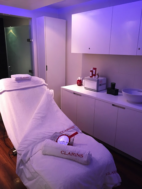 Spa treatment room with white bed, and Clarins towel