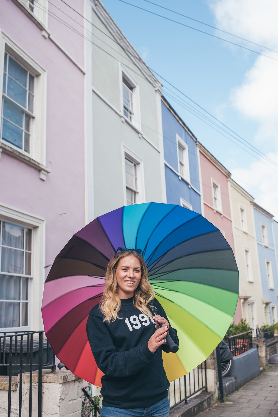Rachel Emily with bright rainbow umbrella twirling in Cliftonwood, Bristol