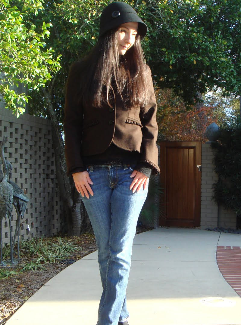 Wearing a black round hat with a brown blazer, black sweater, jeans and black boots.