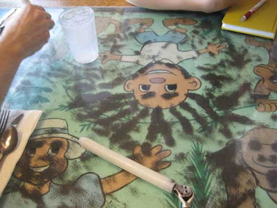 Table transparent top and human and animal cartoons beneath, with dark metal shavings clumped like hair