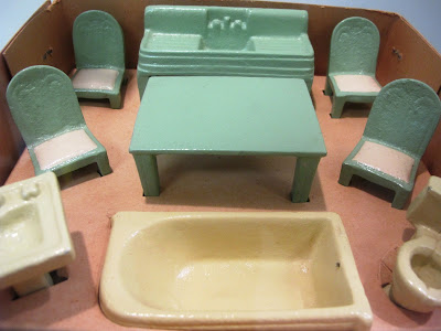 Set of metal dolls' house bathroom and kitchen furniture displayed in its box.
