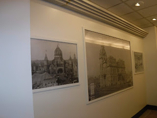white walls on the skywalk level of the Sioux City Orpheum theatre building with 3 large, framed black and white photos showing buildings from Sioux City Iowa around the turn of the 20th century including a corn palace and the old Woodbury County courthouse
