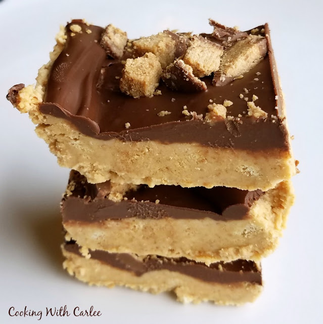 close stack of no bake peanut butter bars with chocolate topping and chopped peanut butter cups on top