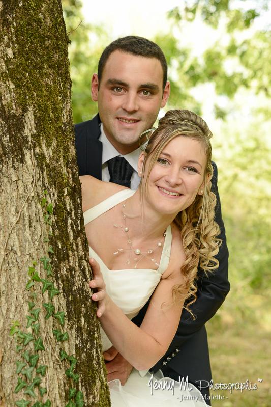 portraits des mariés dans la forêt mariés cachés derrière un arbre