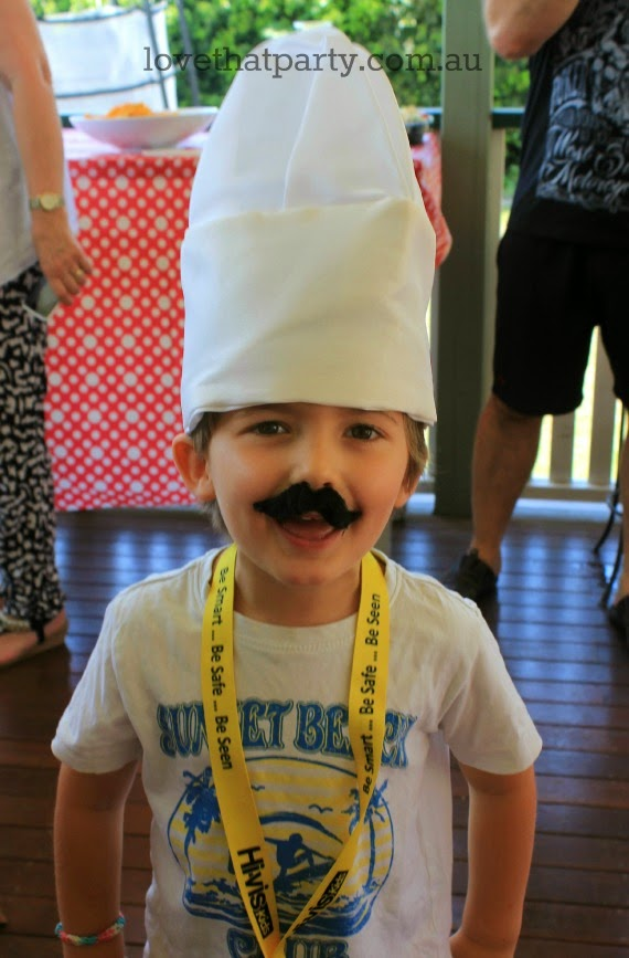 boy with chef hat and fake moustache at pizza birthday party