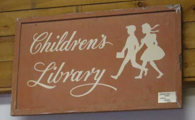 Light brown sign with hand lettered cursive Children's Library, with silhouettes of a girl and boy, probably from the 1940s