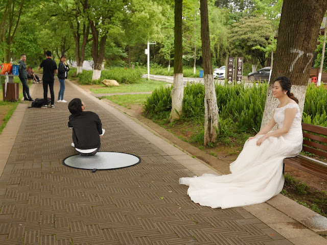young woman wearing a wedding gown sitting on a bench at a park