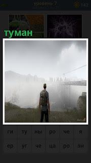 стоит мужчина и смотрит как за туманом скрылся город и мост