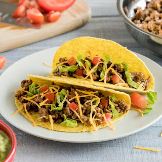 Hard corn shell tacos with beef, lettuce, tomato, and shredded cheese