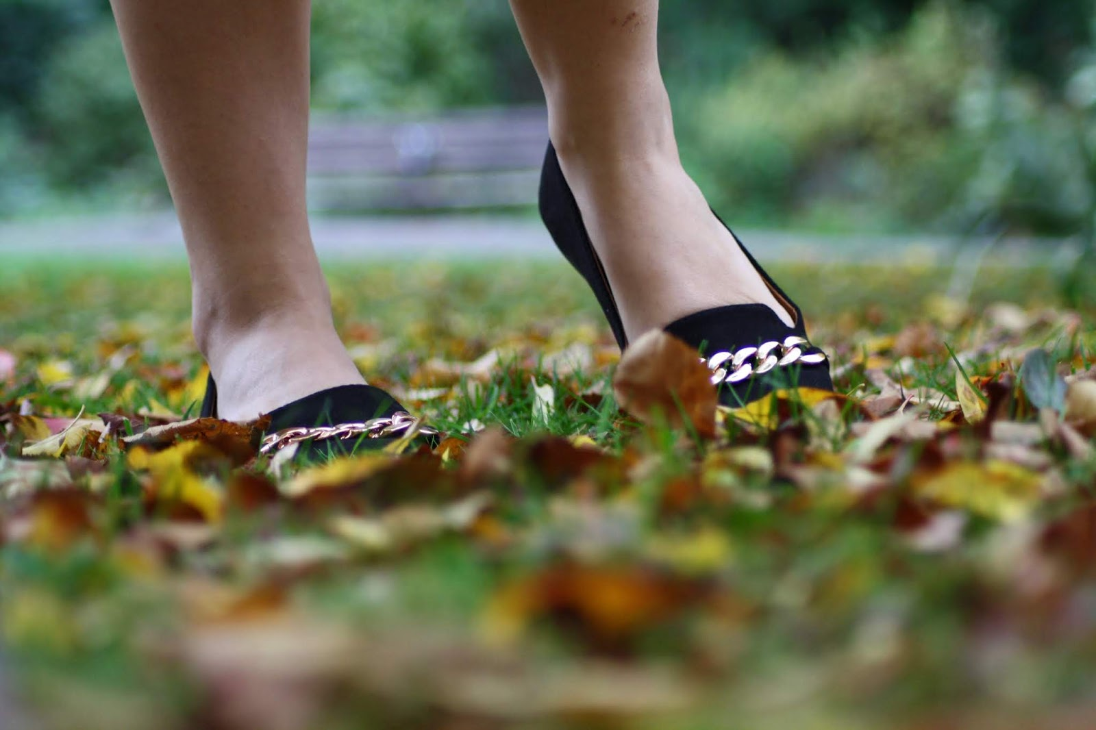 close up of black ballet flat shoes with gold chain amongst fallen autumn leaves