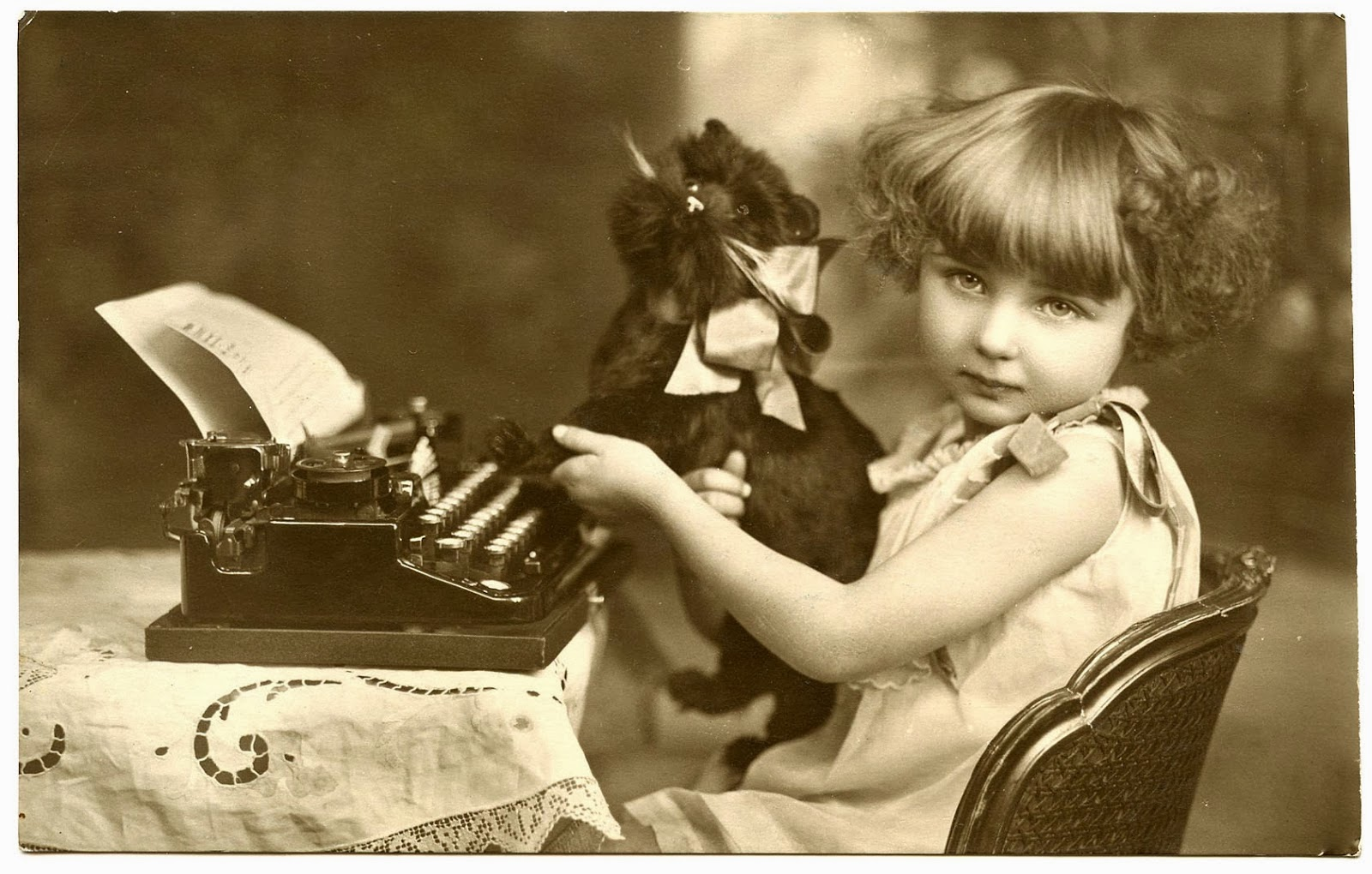 Vintage picture of young girl with toy cat and typewriter