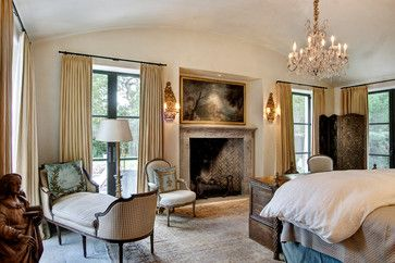 Bedroom with European style and stone fireplace by Eleanor Cummings