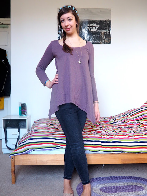 Rapunzel Disneybound outfit of long lavender tunic top, grey skinny jeans, nude ballet flats, and blue flower crown