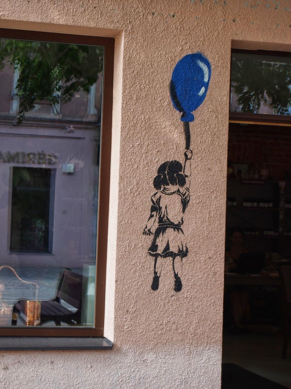 street art of a little girl holding a blue balloon