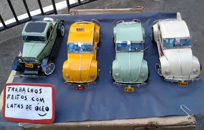 No estande de vendas sobre caixas de papelão, Milton oferece miniaturas do Ford V8 de 1932 e dos famosos Fuscas.