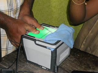 आधार कार्ड के लिए अंगुलियों के निशान देते हुए