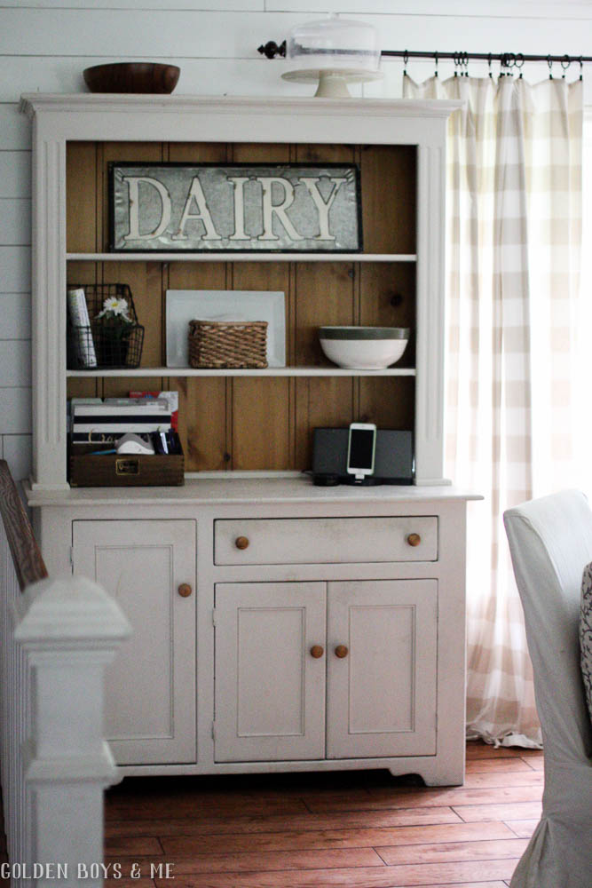 Chalk painted farmhouse style hutch in dining room with dairy sign