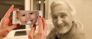 Baby im Smartphone und alte Frau