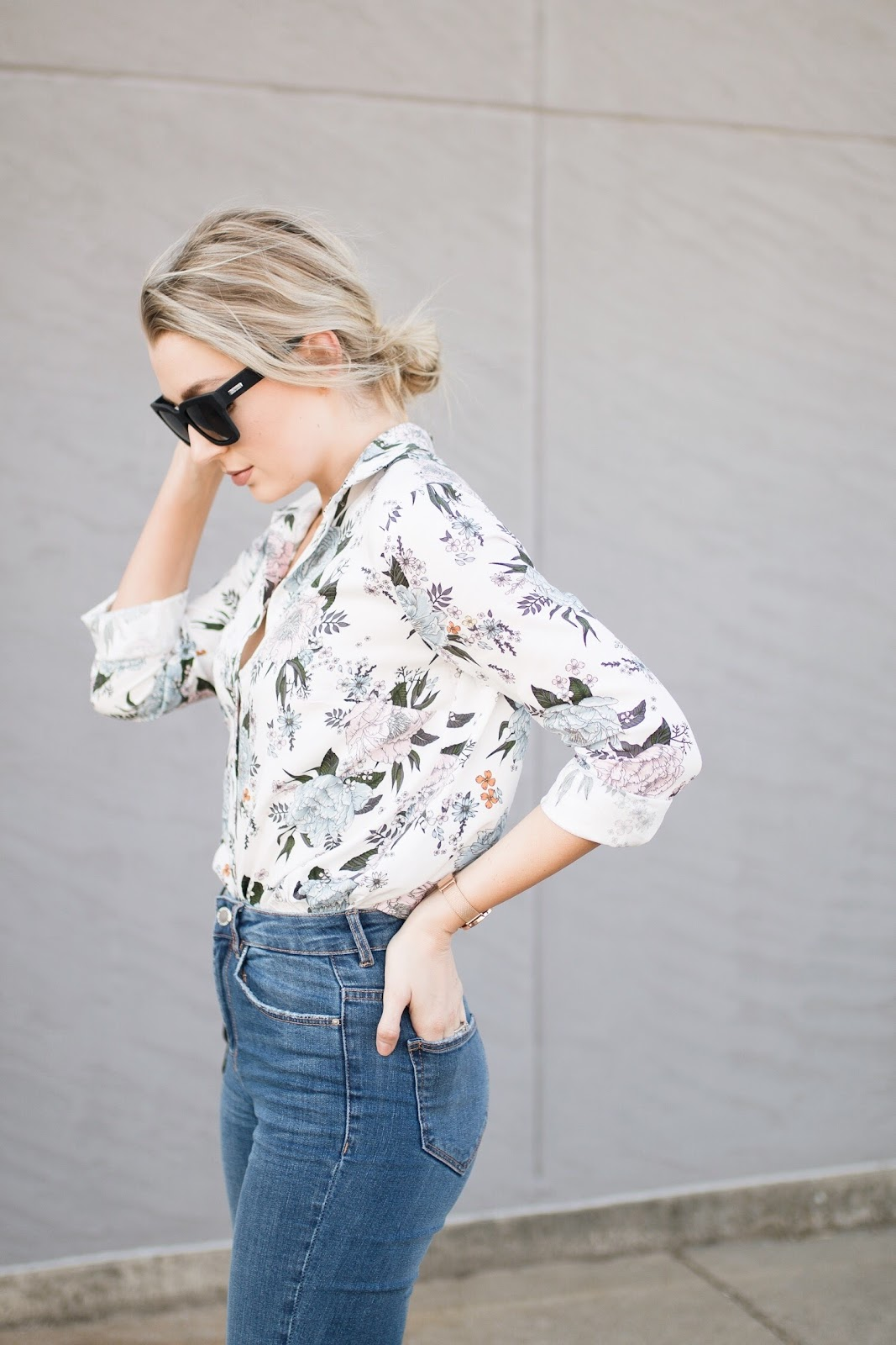 floral top tucked into blue jeans