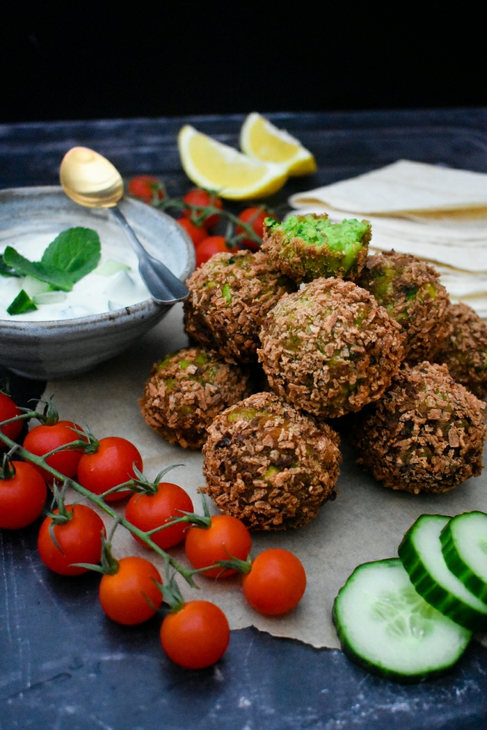 Crisp green falafel made with edamame beans, peas and coriander and served with a yoghurt, cucumber and mint dip. This recipe is easy to make at home and suitable for vegetarians or vegans.