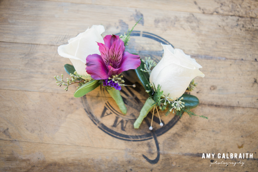 white and purple boutonnieres on a wine barrel