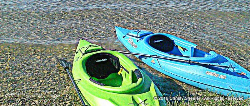 Two kayaks on the lake shore, one green and one blue.  Summer spent on the water is relaxing.
