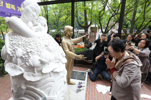 La mujer de consuelo Lee Yong-su se disculpa ante la estatua Vietnam Pieta instalada en Seúl