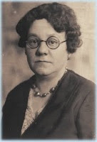 A B&W portrait of a middle-aged, plump white woman with round eyeglasses and short, curly, dark hair.