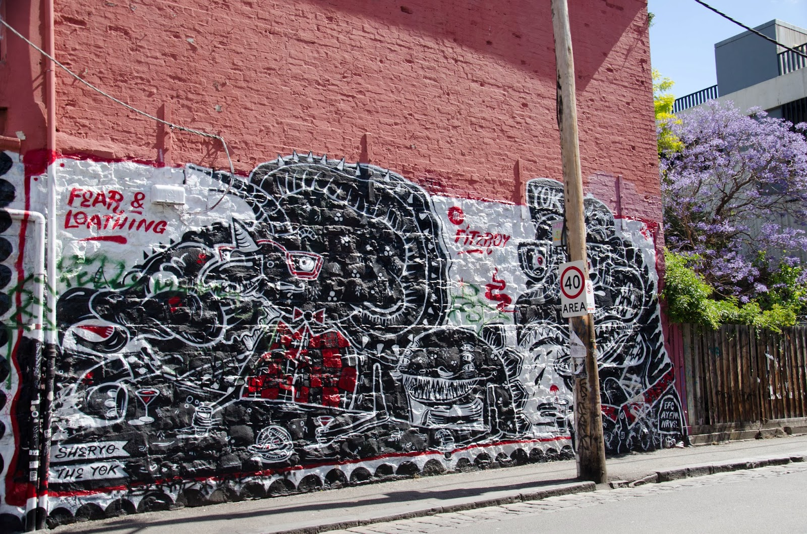 a black and white mural on an orange wall of a building in Brunswick Street.