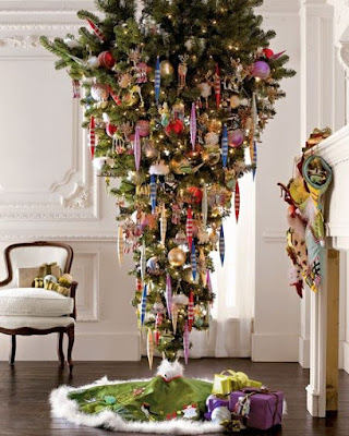 Beautifully decorated upside-down Christmas tree standing between a white chair and a fireplace in a white paneled room