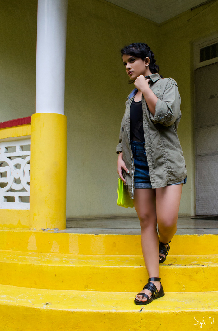An image of a female fashion blogger wearing a sheer cutout bodysuit, a khaki jacket, high waist denim shorts, boxer braids and gladiator sandals for her style blog