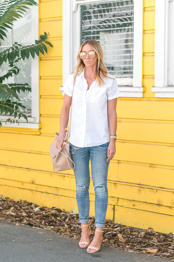 white button up distressed skinny jeans nude pumps beige bag