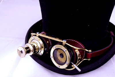 Steampunk goggles worn on top hat. Goggles have one lens that is a telescope, one lens that is a brass aperture shutter from a camera.