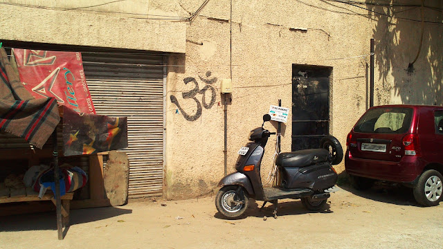 """The sacred Hindu word """"Om"""" written on a wall in Hindi"""