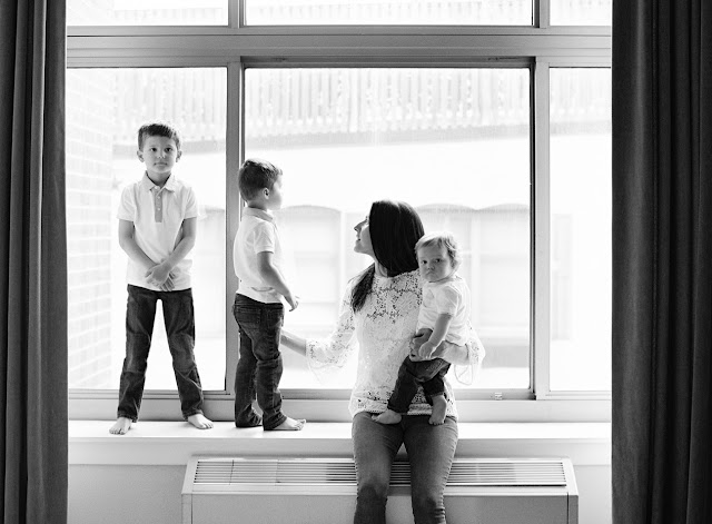 Three sons and mother by the window in the bedroom at home family portraits