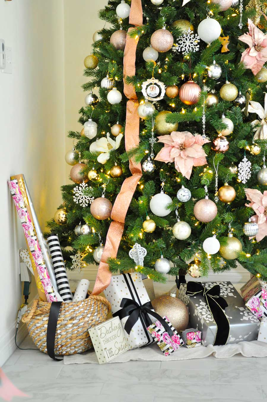 A lucite star tops this blush pink themed Christmas tree filled with pink and white poinsettias plus gold, silver and white ornaments. Such a feminine and classy look!