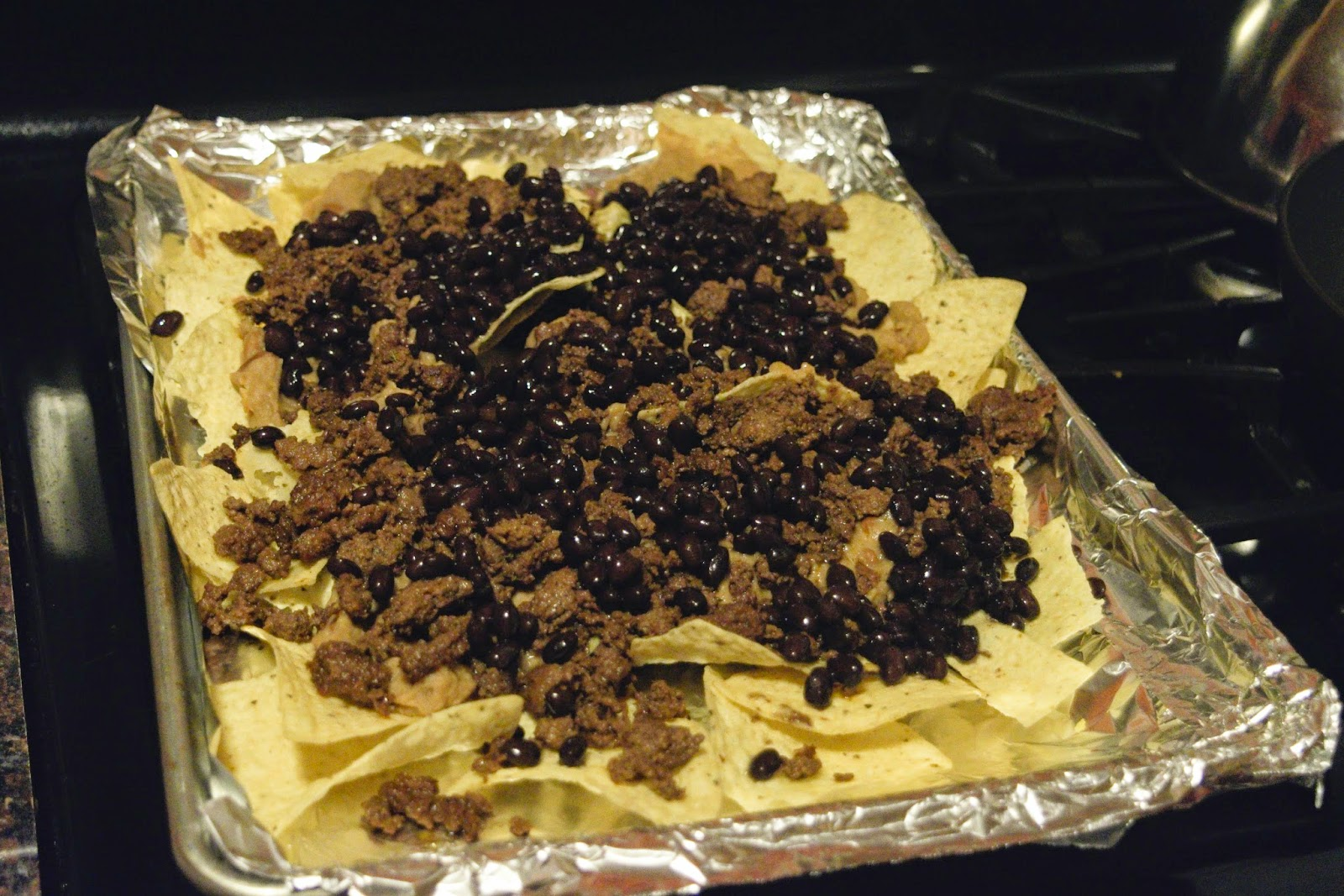 Black beans being added to the Nacho Supreme.