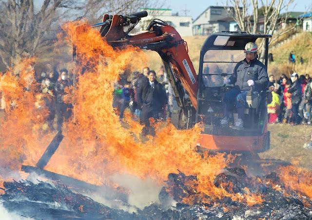 どんど焼きの後処理をするユンボの写真