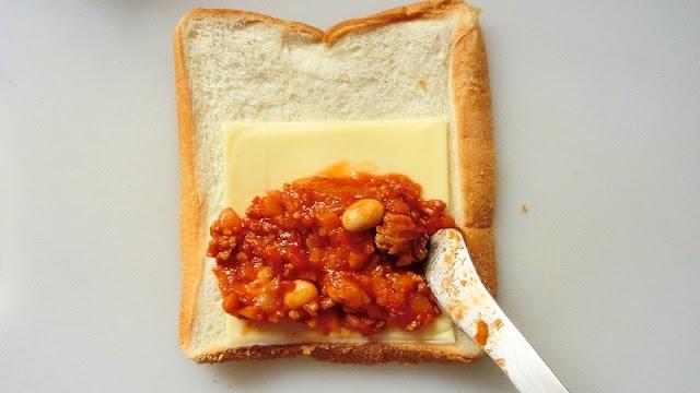 食パンの手間にスライスチーズ、チリコンカンをのせる。