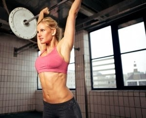 Image of a lady performing the barbell overhead press.
