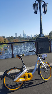 oBike on a bridge over a river. Melbourne in the distance