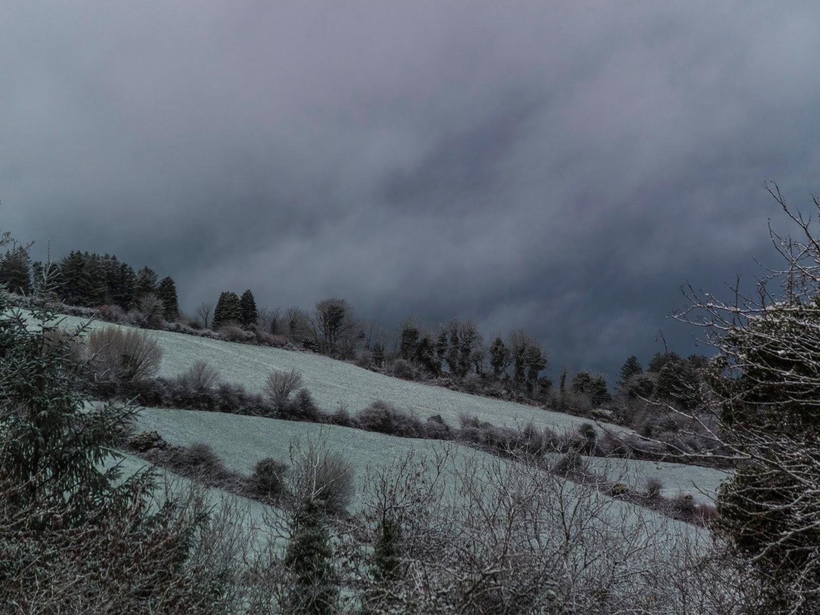 A dark and grey sky above a landscape dusted with snow.